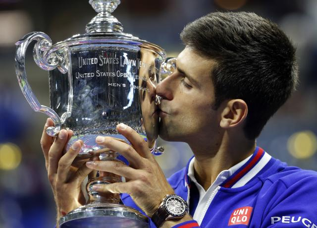 Novak Djokovic, of Serbia, kisses the championship trophy after defeating Roger Federer, of Switzerland, during the men's championship match of the U.S. Open tennis tournament, Sunday, Sept. 13, 2015, in New York. (AP Photo/Julio Cortez)