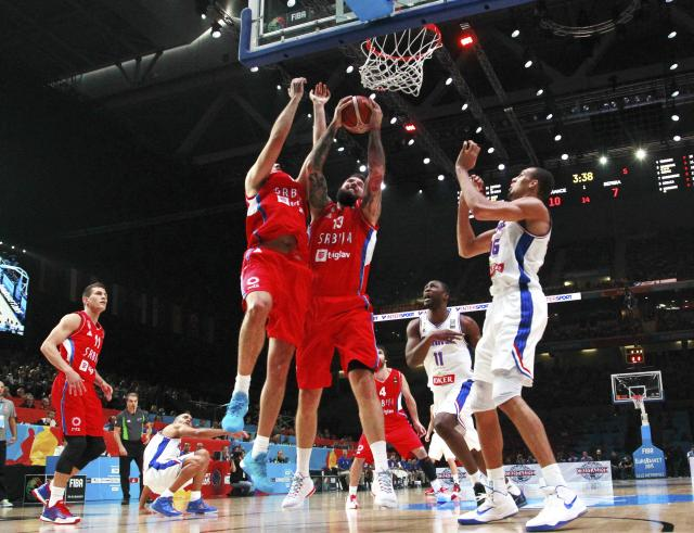 Serbia's Miroslav Raduljica, center, controls the ball during the EuroBasket European Basketball Championship bronze medal match, between France and Serbia, at Pierre Mauroy stadium in Lille, northern France, Sunday, Sept. 20, 2015. (AP Photo/Michel Spingler)